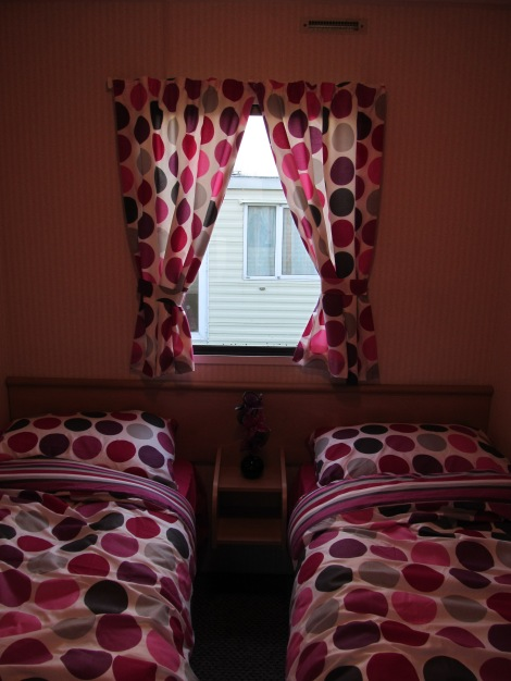 An image showing a caravan bedroom with curtains made from bedding material, An image showing caravan upholstery, curtains, scatter cushions made by Advance Upholstery, Bispham, Blackpool