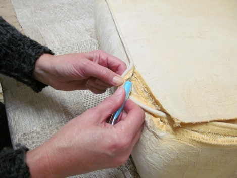 An image showing an upholsterer unpicking a conservatory suite cushion