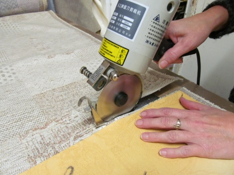 An image showing an unpholsterer using a hand-held cutting to sut out fabric.